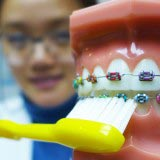 Dr. Jenny Zhu of Manhattan Bridge Orthodontics demonstrates how to brush with braces
